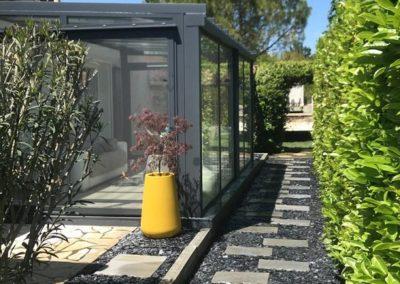 Aménagement paysagers par Avond & Jardins, autour d'une verranda : pas japonais, haie, pelouse